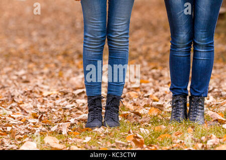 Girls feet boots walking on fall leaves outdoor with autumn season nature on background - Stock Photo