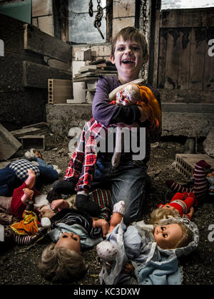 Photo of a creepy young boy holding an old clown doll in an old barn covered in spiderwebs and dust. - Stock Photo