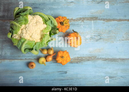 Pumpkin decorative, cauliflower and onions on a rustic blue wooden background. Healthy eating, vegetarian concept. - Stock Photo