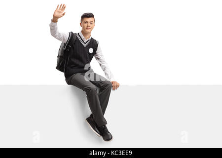 Teenage student in a uniform sitting on a panel and waving at the camera isolated on white background - Stock Photo
