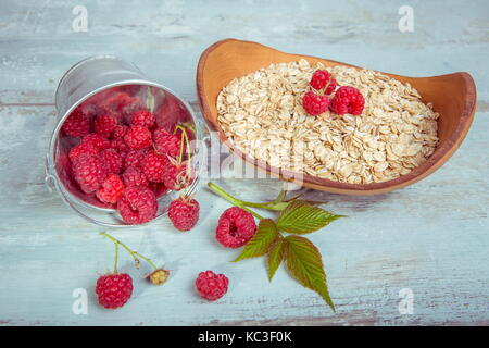 Fresh raspberries in a bucket and oat flakes in a wooden bowl on a rustic wooden background. Healthy diet, vegetarian - Stock Photo