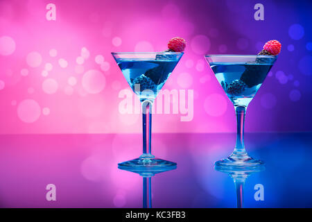 Colorful cocktails garnished with berries, background with light effects - Stock Photo