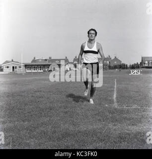 1960s, historical, picture shows a male athlete wearing vest and shorts training alone outside in a grass field, - Stock Photo