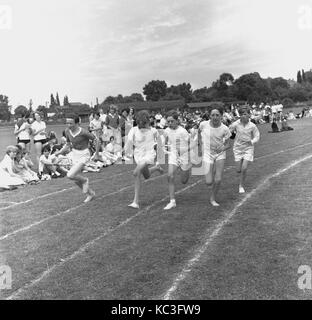 1964, historical, young schoolboys compete in a running race in vests and pilmsolls outside on a grass track, England, - Stock Photo