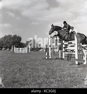 1964, historical, a male show jumper wearing his attire and hat with horse leaps over an obstacle at a outside show - Stock Photo