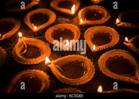 Happy Diwali - Terracotta diya or oil lamps over clay surface or ground, selective focus - Stock Photo