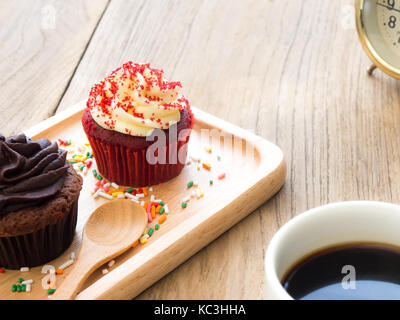Red and chocolate cupcakes put on a spherical wooden plate. Beside of cupcake have Cactus and white coffee mug.All - Stock Photo