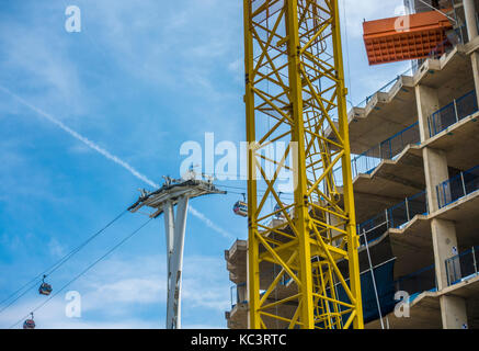 Construction at Greenwich Peninsular in East London, with new build apartment block and crane, and Emirates Air - Stock Photo