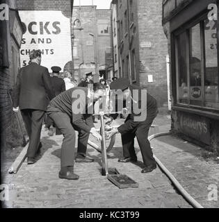 1964, historical, picture shows a fireman and adult male helper trying to put a hosepipe onto a mains water supply - Stock Photo