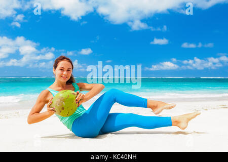 Young woman fitness abdominal exercise on beach to keep fit and health. Doing crunches core, leg raising and twisting - Stock Photo