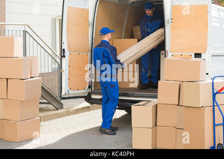 Young male movers unloading rolled up rug from truck on street - Stock Photo