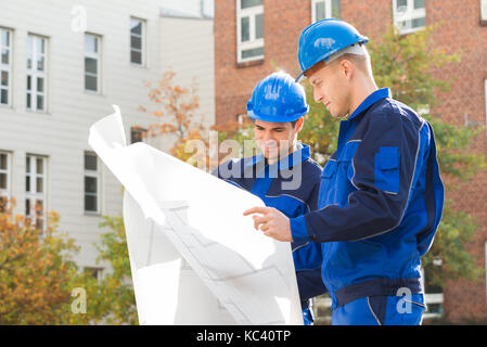 Young male architects analyzing blueprint together outdoors - Stock Photo