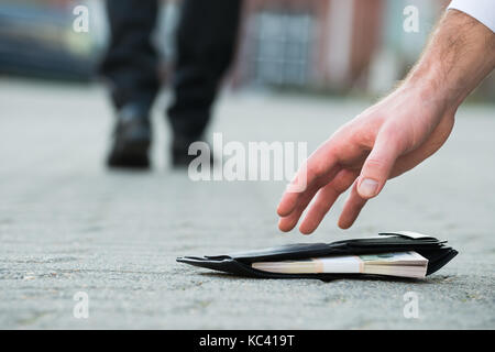 Cropped hand of businessman picking up fallen wallet with money on street - Stock Photo