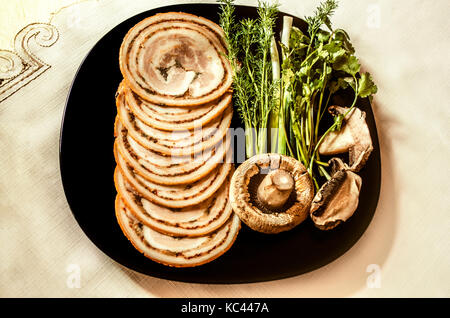 Sliced meatloaf with acute seasonings of smoked pork tenderloin on black plate - Stock Photo