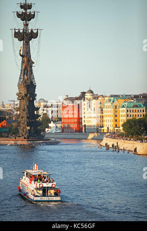 Statue of Peter the Great, monument to Peter I., sightseeing boat and traditional houses in the evening light, river - Stock Photo