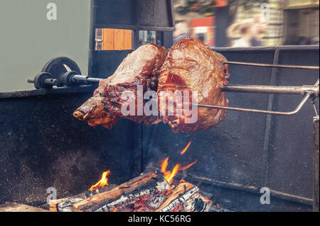A spit for cooking roast shank in Prague on a Sunny day. A big piece of meat. National cuisine. The street food. - Stock Photo