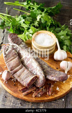 Beef jerky smoked sausage sudzhuk with spices and garlic is served on a cutting board. - Stock Photo
