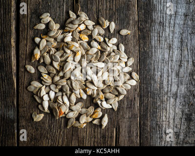 dried pumpkin seeds on old weathered wooden background - Stock Photo
