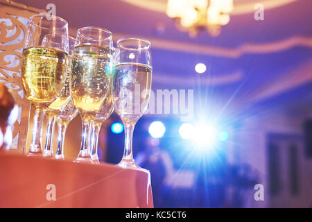 A lot of wine glasses in blue light with a cool delicious champagne or white wine at the bar - Stock Photo