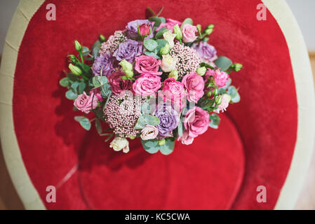 Beautiful bridal bouquet tied with silk ribbons and lace with a key in the form of heart. Roses and branches of - Stock Photo
