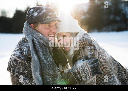 Beautiful senior couple on a walk in sunny winter nature - Stock Photo