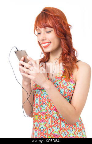 Girl is concentrating on her cell phone and wears a headset. Redhead woman is wearing a colorful summer dress. Fashion - Stock Photo