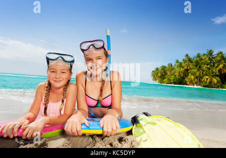 Two girls in snorkeling mask with friends laying on the beach on surfboards having flippers near on tropical island - Stock Photo
