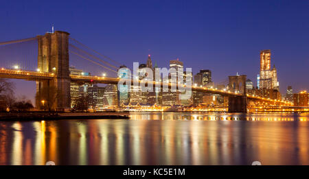 Evening, twilight view of the Brooklyn Bridge and buildings of Lower Manhattan financial district, New York City - Stock Photo