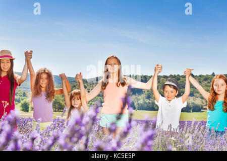 Portrait of six happy age-diverse kids standing together in a row in lavender field, holding hands up at sunny day - Stock Photo