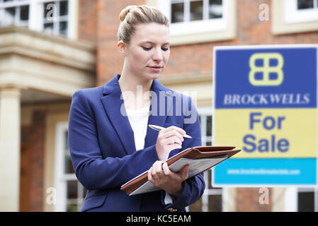 Female Realtor Standing Outside Residential Property With For Sale Sign - Stock Photo