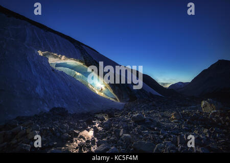Explorer inside an ice cave during a photography expedition in Athabasca Glacier - Stock Photo