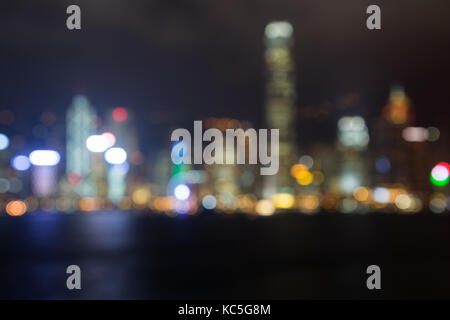 Blurred bokeh city lights of Hong Kong Island's skyline with lit modern skyscrapers at night in Hong Kong, China. - Stock Photo