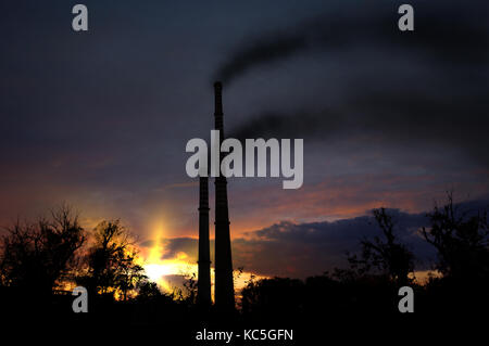Global warming concept - old concrete high chimneys smoking on cloudy sky - Stock Photo