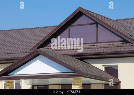 ... House With Plastic Windows And A Brown Roof Of Corrugated Sheet. Roofing  Of Metal Profile