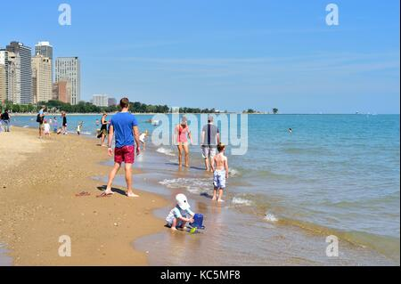 Young boy playing in the sand among people enjoying a summer day at Chicago's Oak Street Beach. Chicago, Illinois, - Stock Photo