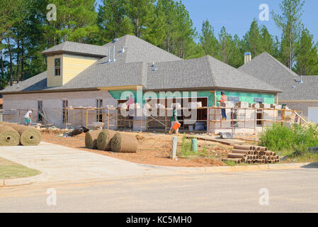 Brick layers working on a new home under construction need to use scaffolding to reach the upper parts of the exterior - Stock Photo
