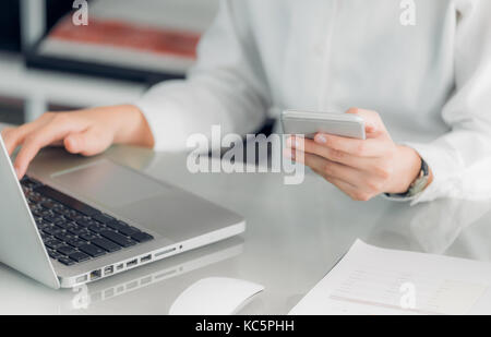 Close up businesswoman holding mobile phone and using laptop computer on office desk,Business communication concept. - Stock Photo