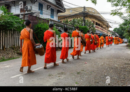 Buddhist monks in a line in Luang Prabang, Laos - Stock Photo