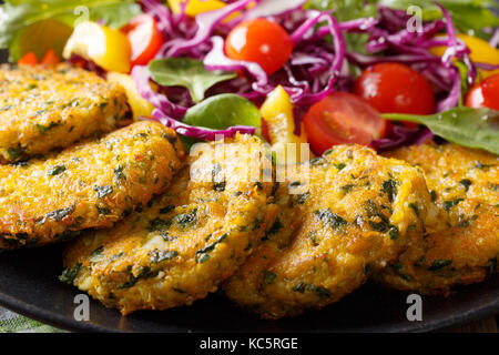 Dietary quinoa with spinach burgers and fresh vegetable salad close-up on a plate. horizontal - Stock Photo