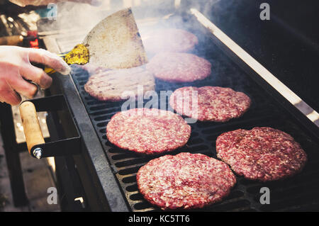 Frozen burger in the cook hand ready for preparing. Round patties of raw minced meat roasted on a metal grid. - Stock Photo