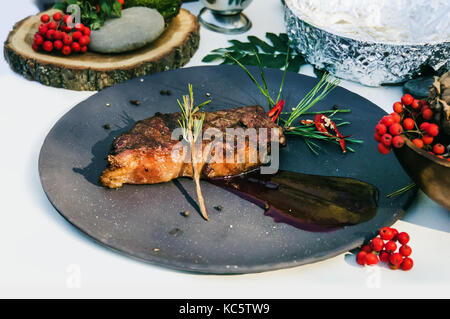 Delicious grilled steak with red sauce with berry cranberries on the plate on a white background. close-up - Stock Photo
