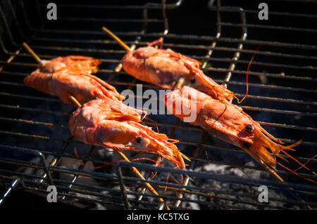 delicious prawn spit on grill with flames. King prawns in the shell fried in the fire. - Stock Photo
