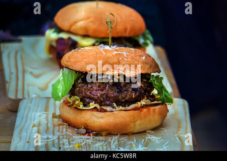 Home made hamburger with lettuce, cheese, beef meat and french fries placed on old wooden table. Two big tasty Burger - Stock Photo