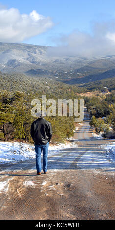 Man, dressed in jeans and black coat, walks down a snowy road in Tijeras, New Mexico.  Gravel road disappears into - Stock Photo