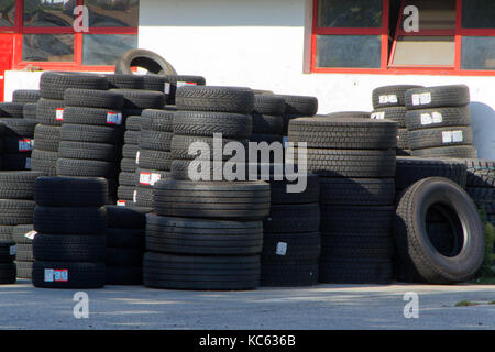 Tires for sale at a tire store - stacks of new tires - Stock Photo