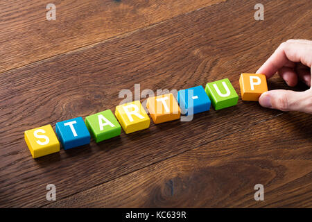 High Angle View Of A Start-up Concept On Colorful Blocks At Wooden Desk. Entrepreneurship Concept - Stock Photo