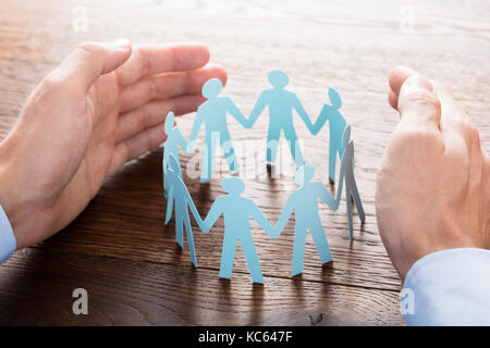 Close-up Of Businessperson Protecting Cut-out Figures On Wooden Desk - Stock Photo