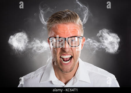 Furious Young Businessman With Red Forehead And Smoke - Stock Photo