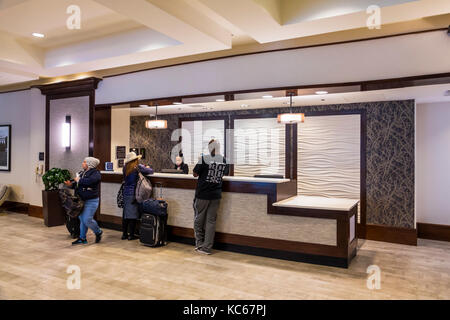 Washington DC District of Columbia Homewood Suites by Hilton hotel front desk reservations Black woman agent guest - Stock Photo