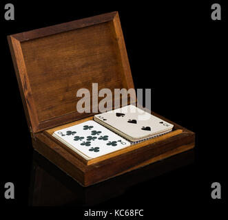 Vintage wooden box with two complete white playing cards decks set, on black background and reflective surface - Stock Photo
